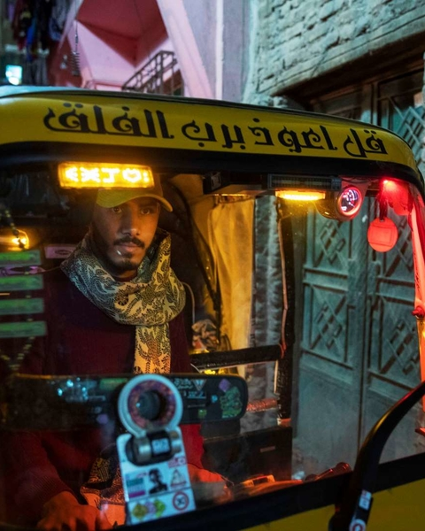 A driver manoeuvres his tuk-tuk in a narrow alleyway