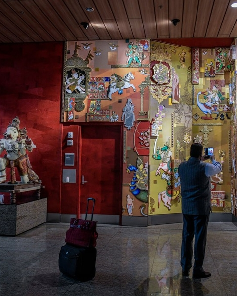 """Moving Constant,"" a gilded depiction of Indian gods and goddesses, is a popular photo spot on the domestic departures level of Terminal 2."