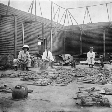 Interior of Oba's compound burnt during seige of Benin City (present day Nigeria) , with bronze plaques in the foreground and three British soldiers of the Benin Punative Expedition 9-18 February 1897.